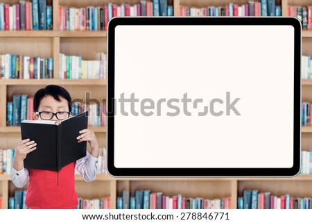 Cute little schoolboy reading a book in the library near a blank board - stock photo