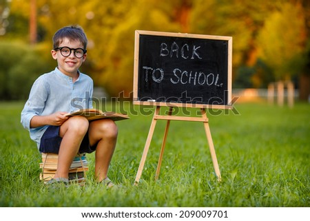 Cute little schoolboy reading book  - stock photo
