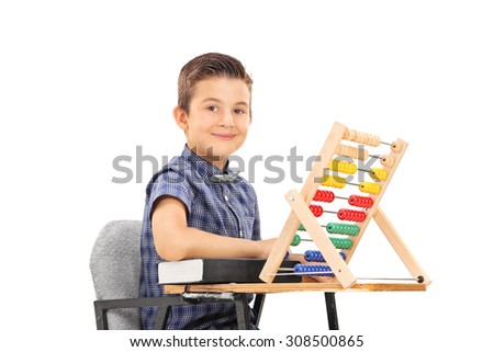 Cute little schoolboy sitting at a school desk with a book and an abacus on it isolated on white background - stock photo