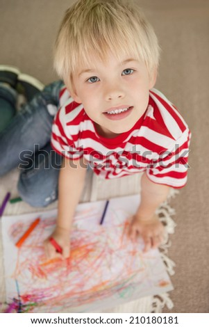 Cute little schoolboy smiling at camera while drawing at the elementary school