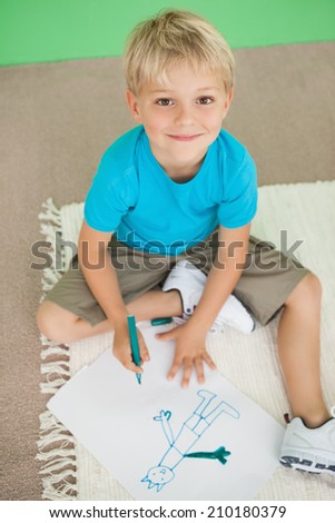 Cute little schoolboy smiling at camera while drawing at the elementary school - stock photo