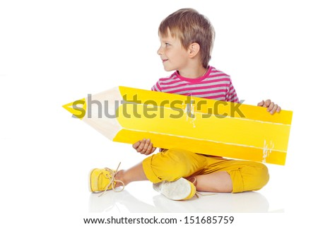 Cute little schoolboy with a pencil and looking at camera - stock photo