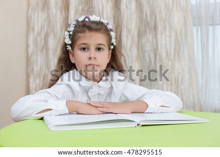 Cute little schoolgirl pondered. BEAUTIFUL GIRL ON THE OPEN BOOK .Child had a serious expression on his face. It is elementary school student. Back to school.