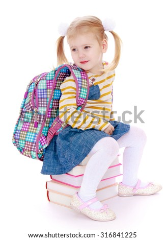 Cute little schoolgirl with long tails on his head sat down on a stack of textbooks-Isolated on white background - stock photo