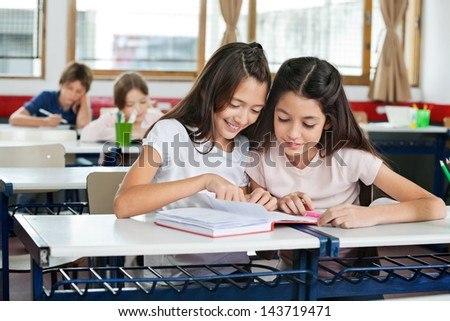 Cute little schoolgirls studying together at desk with classmates in background - stock photo