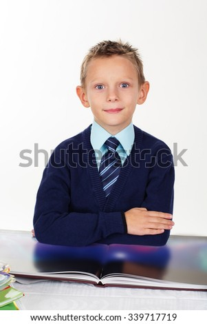 Cute little serious preschooler boy is wearing official clothes looking at pictures in a book, isolated over white background - stock photo
