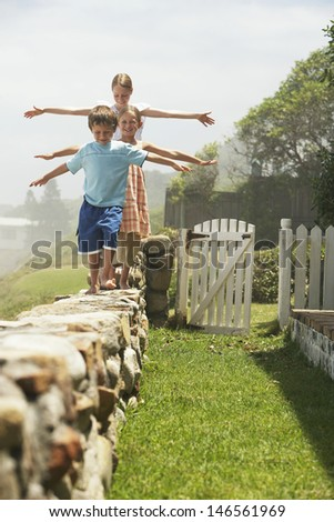 Cute little siblings balancing while walking in a row on stone wall at ...