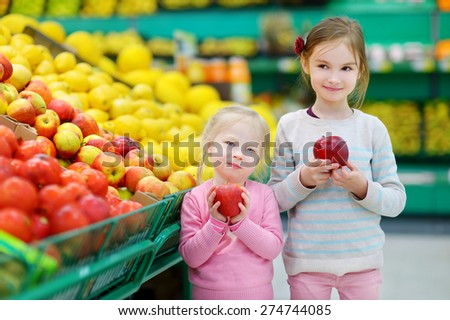 Cute little sisters choosing apples in a food store or a supermarket - stock photo