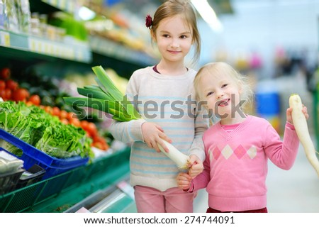 Cute little sisters choosing vegetables in a food store or a supermarket