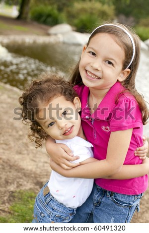 Cute little sisters playing outside - stock photo