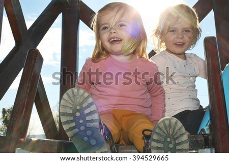 Cute little sisters plying in the backyard.  - stock photo