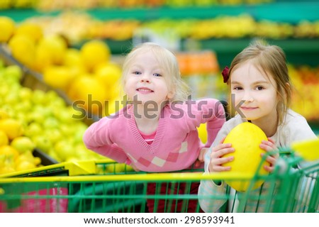 Cute little sisters shopping in a food store or a supermarket - stock photo