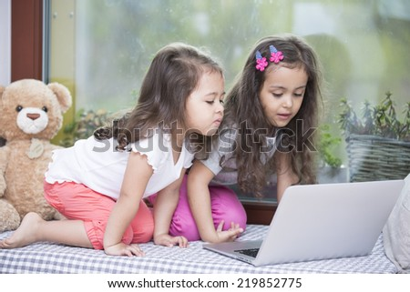 Cute little sisters using laptop on bed at home - stock photo