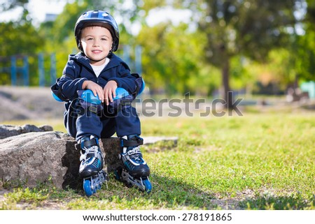 Cute little skater boy sitting on the stone in the park - stock photo