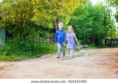 cute little smiling blond boy and girl (brother and sister) with a bouquet of lilac in the hands in a lavender dress and a blue shirt