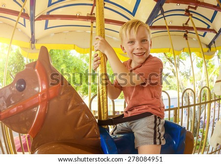 Cute little smiling boy riding on a Carnival Carousel at an amusement park or theme park. Warm afternoon sun in the background - stock photo