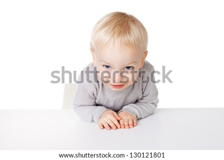 Cute little smiling boy sitting at table isolated on white background - stock photo