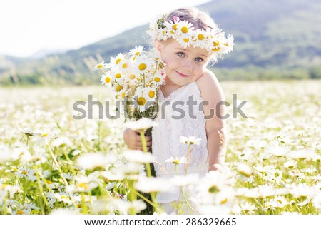 Cute little smiling girl in the chamomile field in spring - stock photo