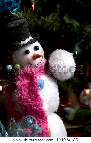 Cute little smiling snowman under Christmas tree with snow ball in his hand - stock photo