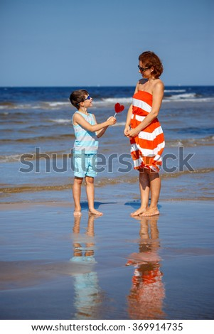 Cute little son giving red candy in shape of heart to his mother during beach vacation on warm summer day - stock photo