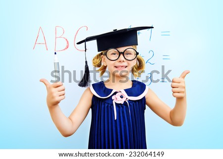 Cute little student girl in academic hat during the lesson at school. Educational concept. - stock photo