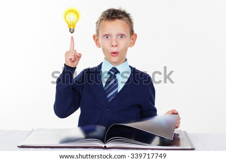 Cute little surprised preschooler boy with a raised finger and bulb is wearing official clothes, isolated over white background - stock photo