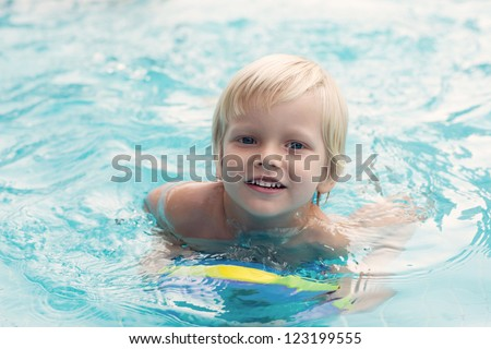 Cute little swimmer courageously overcoming water barrier - stock photo