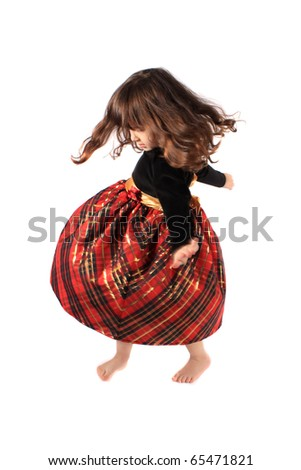 Cute little three year old girl in a fancy plaid and velvet dress dancing and twirling on a white background with selective focus and motion blur - stock photo