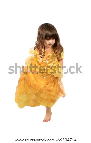 Cute little three year old girl in a fancy princess dress dancing on a white background