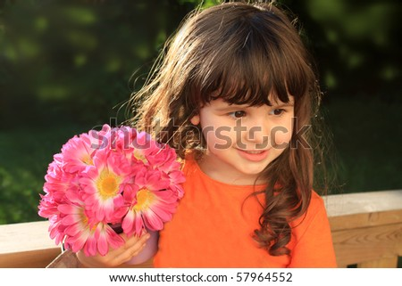 Cute little three year old girl smiling and holding pink flowers - stock photo