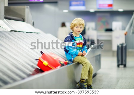 Cute little tired kid boy at the airport, traveling. Happy child waiting with kids suitcase on baggage carousel. Canceled flight due to pilot strike. - stock photo