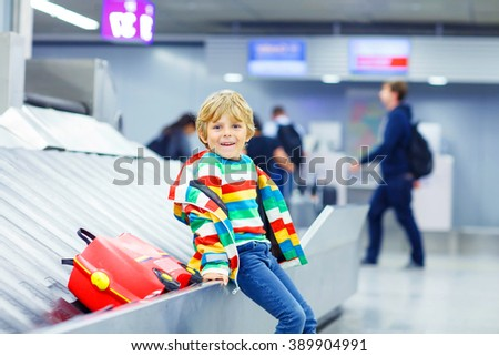 Cute little tired kid boy at the airport, traveling. Smiling child waiting with kids suitcase on baggage carousel. Canceled flight due to pilot strike. - stock photo