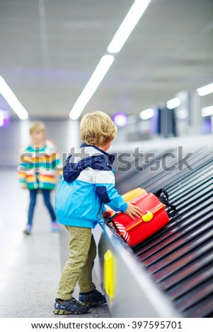 Cute little tired kid boy at the airport, traveling. Upset child waiting with kids suitcase on baggage carousel. Canceled flight due to pilot strike. - stock photo