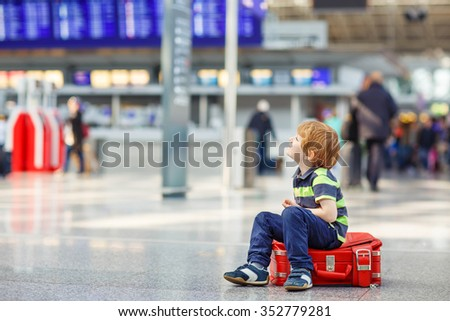 Cute little tired kid boy sitting on suitcase at the airport, Sad child waiting with big suitcase. Canceled flight due to pilot strike. - stock photo