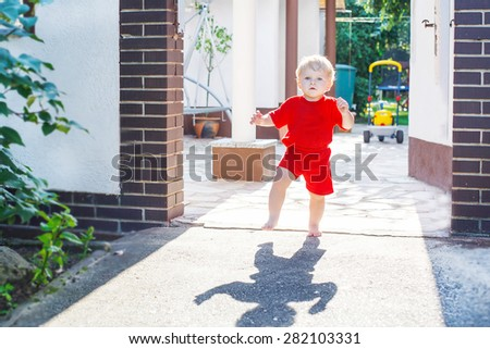 Cute little toddler baby boy making his first steps outdoors. Happy kid learning walking. - stock photo