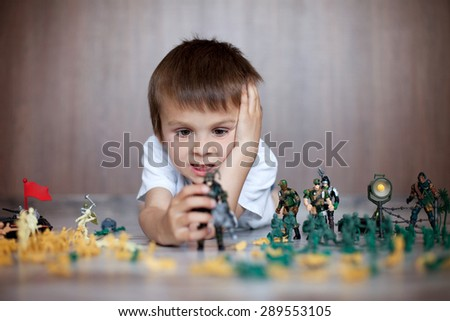 Cute little toddler boy, playing at home with soldiers and figurine toys, playing wars and peace - stock photo