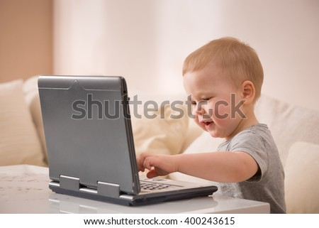 Cute little toddler boy sitting on the sofa with his laptop. Learning with technology. Early development. Child and computer. - stock photo