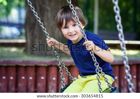 Cute little toddler boy, swinging in the park, summertime, having fun outdoors - stock photo