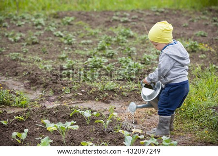 Cute little toddler boy watering plants in the garden. Adorable little child helping parents to grow vegetables. Activities with children outdoors.  - stock photo