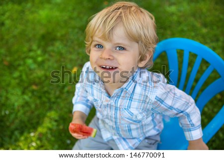 Cute little toddler boy with blond hairs eating watermelon in summergarden