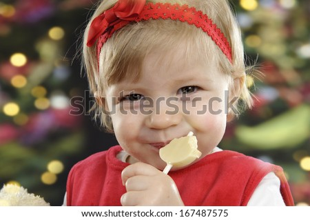 Cute little toddler eating a chocolate lolly, christmas lights in the background