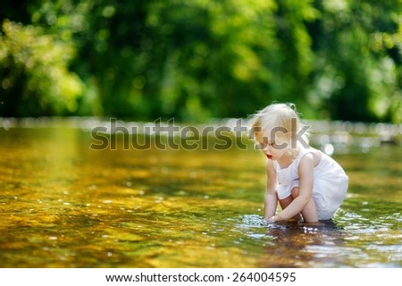 Cute little toddler girl having fun by a river on warm and sunny summer day - stock photo