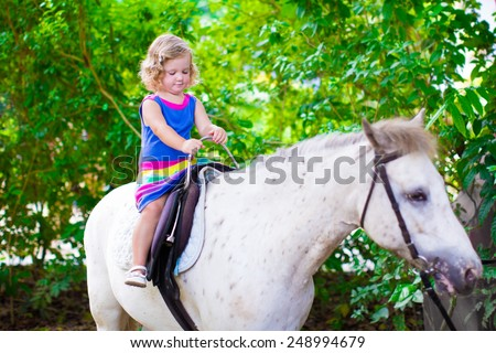 Cute little toddler girl having fun on a horse ride enjoying family trip to a zoo on a hot summer day - stock photo