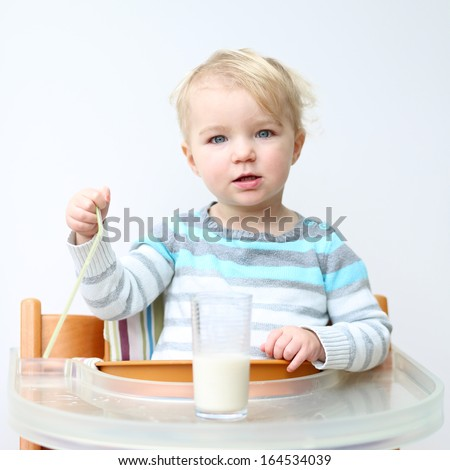 Cute little toddler girl in blue stripes sweater drinking milk from the glass with straw sitting indoors in high feeding chair against white wall - stock photo