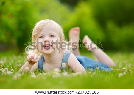 Cute little toddler girl laying in the grass on a sunny summer day