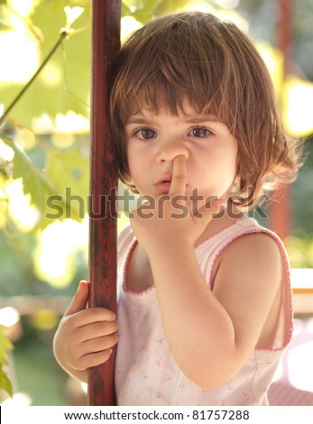 Cute little toddler girl picking her nose - stock photo