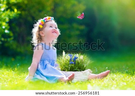 Cute little toddler girl with curly hair wearing a blue summer dress having fun watching a butterfly and flowers, relaxing in the garden on a sunny spring day - stock photo