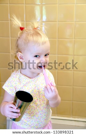 Cute little toddler girl with tooth-brush in her mouth - stock photo