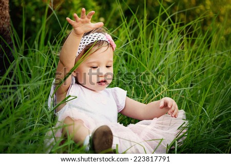 Cute little toddler having fun in the grass - stock photo