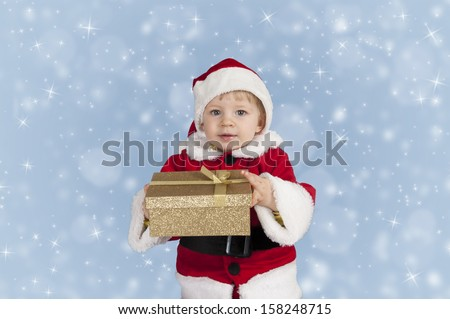 cute little toddler in xmas outfit giving a present - stock photo